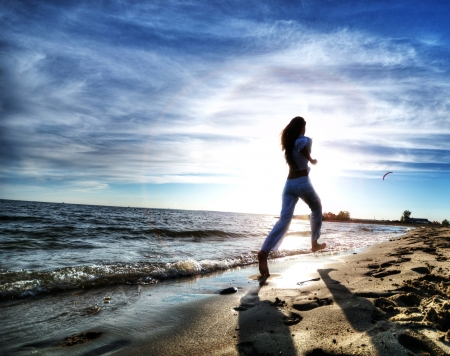 Beautiful young sport woman running on water at sea coast. Sunset with dramatic sky photo