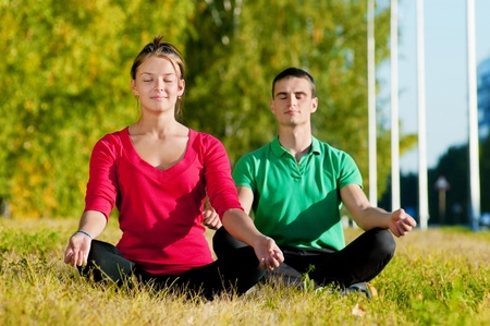 Young man and woman woman doing yoga in the sunny summer park photo
