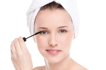 Close-up portrait of young beautiful woman with brush for make-up. Eyelashes zone photo