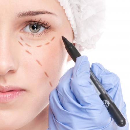 美容師タッチし、女性の顔に訂正線を描画します。前に整形手術依らざる。白で隔離されます。