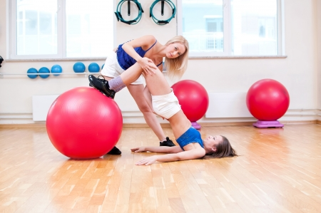 ball stretching: Two smiling women do stretching exercise in sports club. Fitness gym