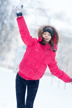 Happy young woman plays with a snow outdoor. Winter day photo
