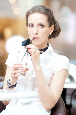 Portrait of beautiful business woman drinking water at office  photo