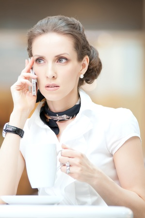 Smart businesswoman talking on the phone in a coffee shop photo