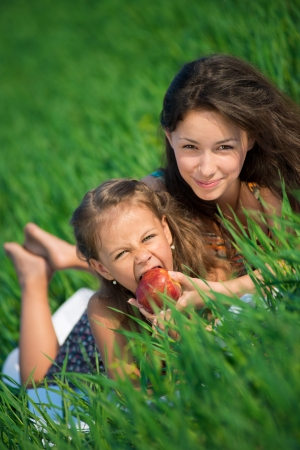 Happy girls with red apple on green grass at spring or summer park picnic photo