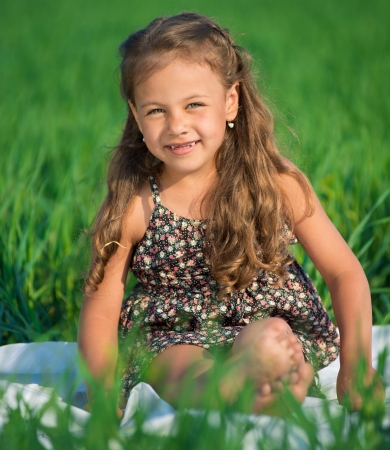 Happy girl on green grass at spring or summer park picnic photo