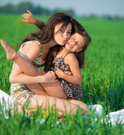 Happy girls embrace and playing on green grass at spring or summer park picnic photo