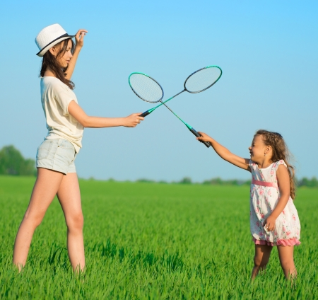 The young girls plays with a racket in badminton over green grass photo