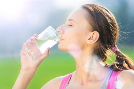 Portret van jonge mooie donkerharige vrouw, gekleed in roze t-shirt drinkwater na sport oefening in de zomer groen park Stockfoto