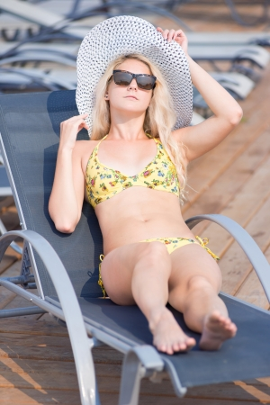 Young woman in bikini, sunglasses  and hat in swimsuit laying on chaise-longue and sunbathing by the pool in a summer vacation  photo