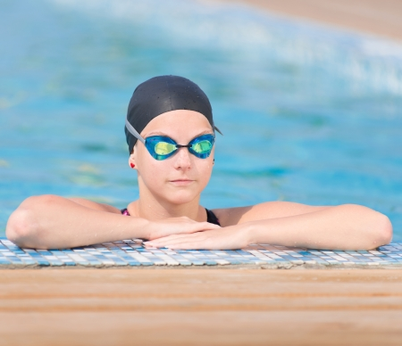 Portrait of a female swimmer wearing a swimming cap and\ goggles in blue water swimming pool. Sport woman.