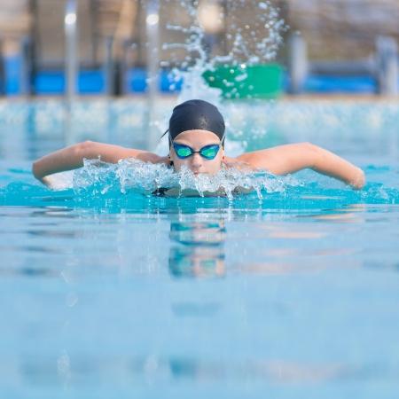 ゴーグルとキャップの青い水のプールに泳ぎにバタフライ スタイルの少女 写真素材 - 20529691