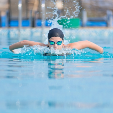 Young girl in goggles and cap swimming butterfly stroke style in the blue water pool Imagens