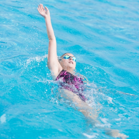 Young girl in goggles and cap swimming back crawl stroke style in the blue water pool photo