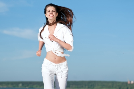 Beautiful young sport woman running in sea coast on sunny summer day  photo