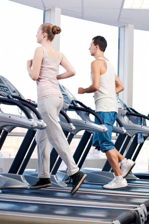 Young woman and man at the gym exercising. Run on a machine.  photo