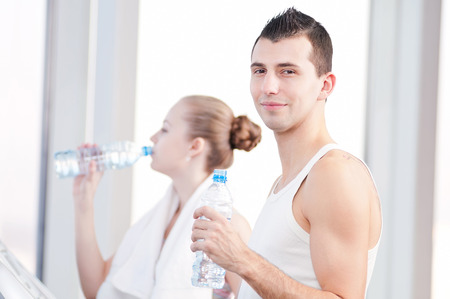 Man and woman drinking water after sports. Fitness gym. photo