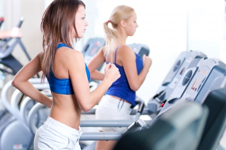 Two young sporty women run on machine in the gym centre photo