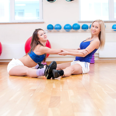 Two smiling women do stretching exercise in sports club. Fitness gym photo
