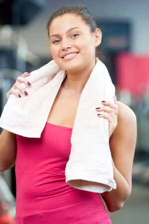 Young woman drinking water after sports. Fitness gym.  photo