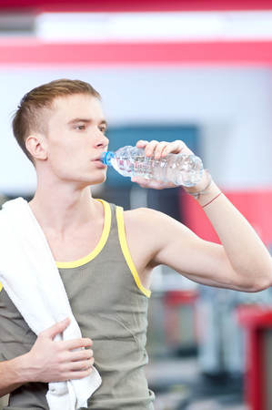 Young man drinking water after sports. Fitness gym.  photo