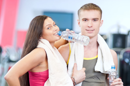 Man and woman drinking water after sport exercises. Fitness gym.  photo