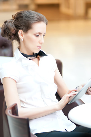 Young professional businesswoman sitting at table at cafe and using tablet on lunch break photo