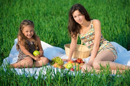 Happy girlswith fruits on green grass at spring or summer park picnic photo