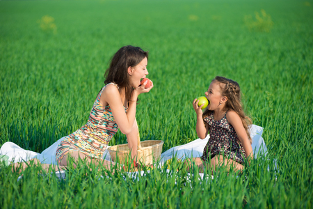 Happy girls with fruits on green grass at spring or summer park picnic photo