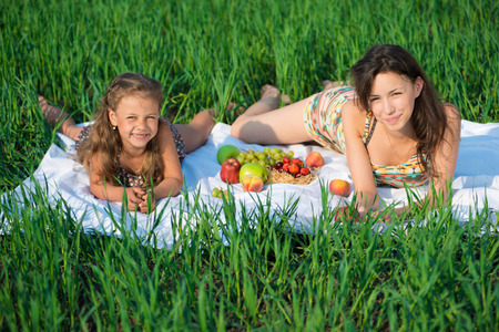 Happy girls on green grass at spring or summer park picnic with fruits photo