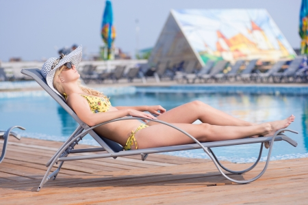 Young woman in bikini, sunglasses,  hat and swimsuit laying on chaise-longue and sunbathing by the pool in a summer vacation  photo
