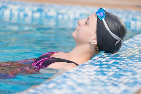 Portrait of a female swimmer wearing a swimming cap and goggles in blue water swimming pool Sport woman
