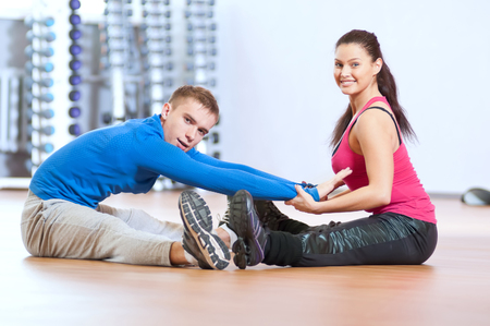 Young man and woman at the fitness gym is doing stretching exercises photo