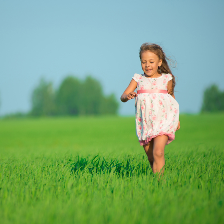 Young happy girl running at green wheat field with her friend together