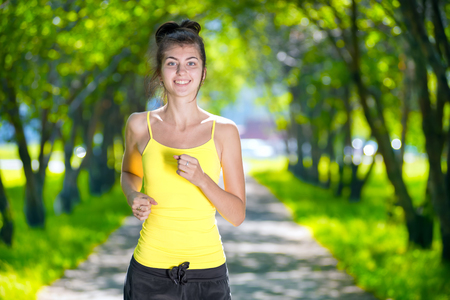 Young woman running outdoors in green park at lovely sunny summer day. Jogging photo