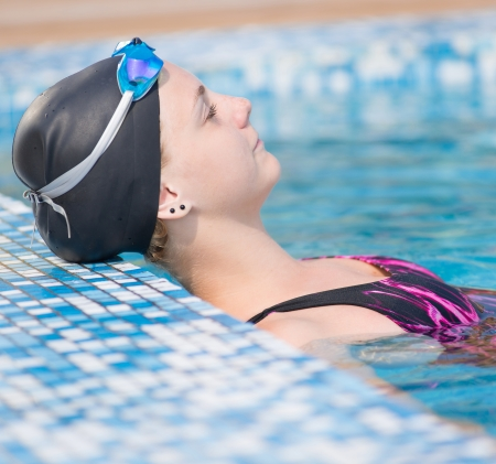 Portrait of a female swimmer wearing a swimming cap and goggles in blue water swimming pool. Sport woman. photo