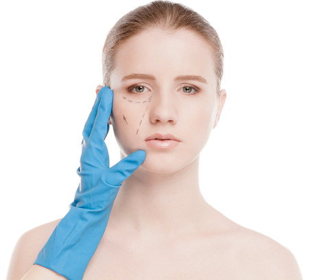 Beautician touch and draw correction lines on woman face. Before plastic surgery operetion. Isolated on white photo