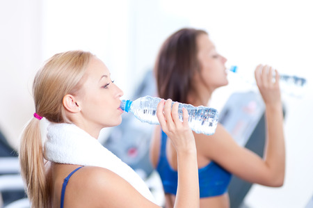 Two young women drinking water after sports. Fitness gym. photo
