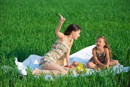 Happy girls on green grass at spring or summer park picnic. One girl point upside photo