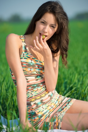 Happy girl with grape on green grass at spring or summer park picnic photo