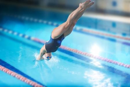 picada: Retrato de una nadadora, que saltando y sumergi�ndose en el deporte piscina cubierta. Mujer deportiva.
