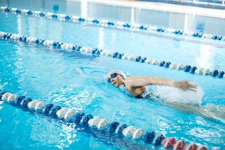 swimmer: Young woman in goggles and cap swimming front crawl stroke style in the blue water indoor race pool