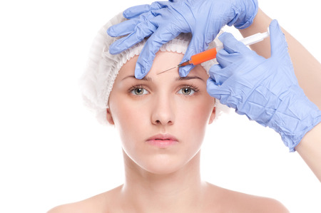 Cosmetic botox injection in the female face. Eye and eyebrow zone. Isolated on white photo