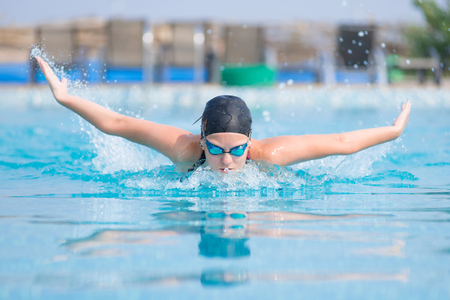 Young girl in goggles and cap swimming butterfly stroke style in the blue water pool photo