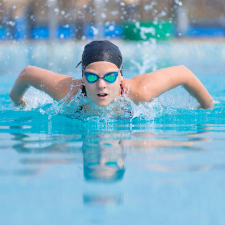 Young girl in goggles and cap swimming butterfly stroke style in the blue water pool Standard-Bild