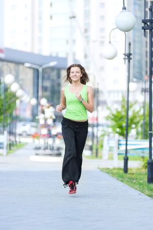 Running woman jogging in city street park at beautiful summer\ morning. Sport fitness model caucasian ethnicity training\ outdoor.