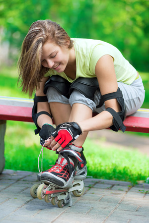 Woman skating in park. Girl going rollerblading sitting on bench  putting on inline skates. Sporty caucasian woman in outdoor fitness activities.  Stok Fotoğraf