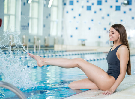 Portrait of a young woman with long hairs near swimming pool. Relaxing after fitness exercises and splashing water. Indoor sport pool with blue water. photo