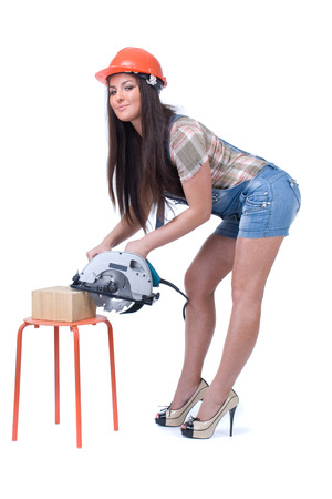 Young sexy female dressed in jeans and orange helmet holding an electric circular disk saw. On a white isolated  photo