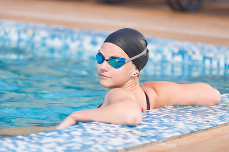 swim cap: Portrait of a female swimmer wearing a swimming cap and goggles in blue water swimming pool. Sport woman. Stock Photo